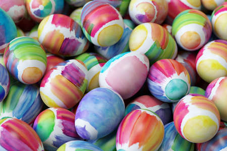Many Easter eggs painted with water paint on a heap at Easter