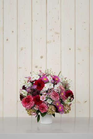 Big flower bouquet in spring in front of a light wood background (3D rendering) Фото со стока