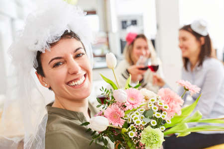 Happy bride with bridal veil and bridal bouquet celebrates the wedding with friends
