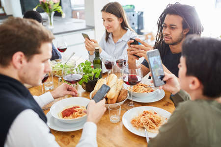 Group people eating together at table looks at smartphone screen Archivio Fotografico