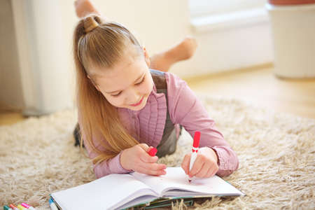 Child paints a picture at home with a felt pen