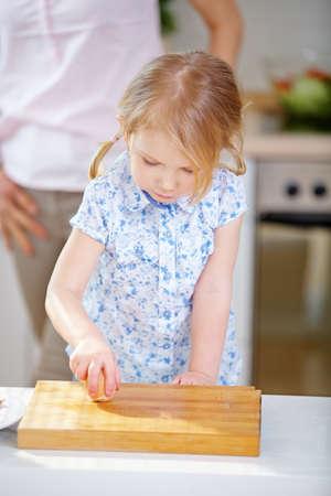 Child breaks an egg in the kitchen for breakfast 免版税图像