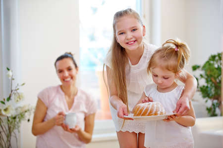 Family with cake and two smiling children at home