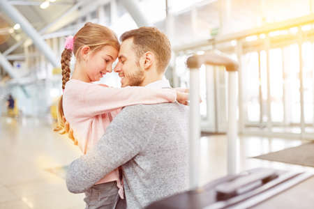 Daughter saying goodbye to father at the airport before a trip