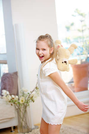 Girl throwing her cuddly toy at home