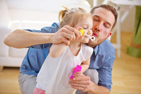 Father and daughter blow soap bubbles together at home 免版税图像