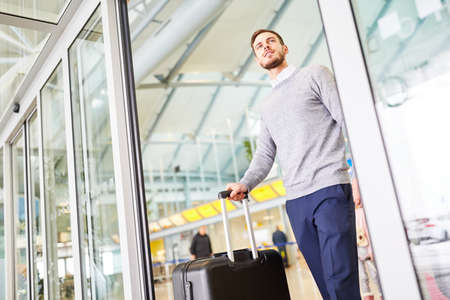 Man as a passenger with trolley in the airport when changing trains or on arrival