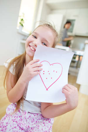 Happy girl shows a sheet of paper with a red heart