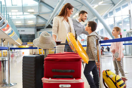 Happy family with a lot of luggage in airport terminal is traveling in summer vacations 免版税图像