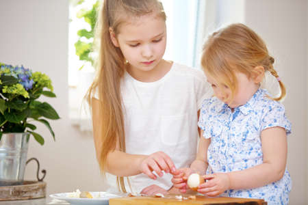 Two girls peel eggs in the kitchen for Easter