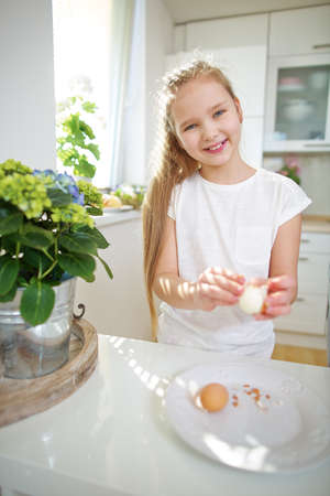 Child peels an egg for Easter in the kitchen