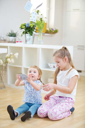 Two children throw cards high in the air while playing