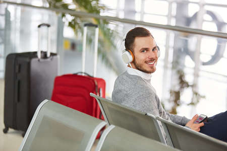 Man as a passenger in the waiting area in the airport lists to music via headphones and smartphone