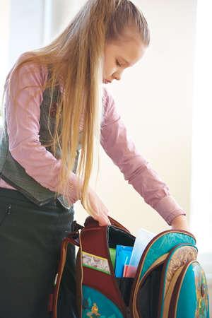 Girl at home unpacks her school backpack 免版税图像