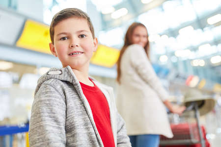 Boy and mother in the airport terminal when changing trains or before leaving for vacation