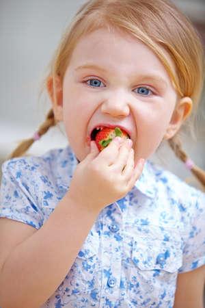 Small child bites into a ripe strawberry at home