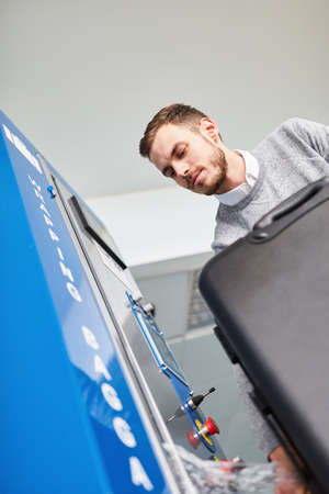 Man as a passenger at the luggage-wrapping machine wraps a suitcase in plastic wrap
