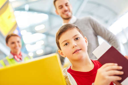 Boy with passport at check in counter in airport terminal with father in background