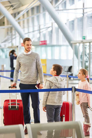 Father and two children with luggage in the airport terminal fly together on vacation 免版税图像
