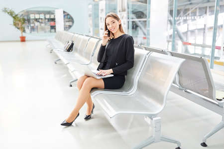 Businesswoman with laptop PC is talking on the mobile phone in airport terminal before the flight