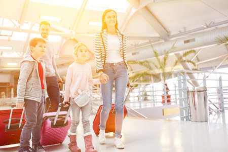 Family on vacation at the airport with children and luggage on travel
