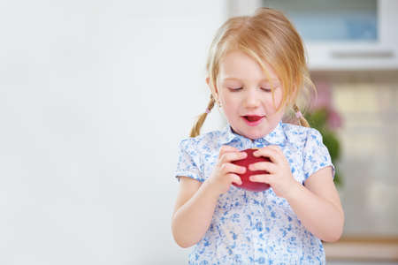 Blonde girl eats a red apple at home