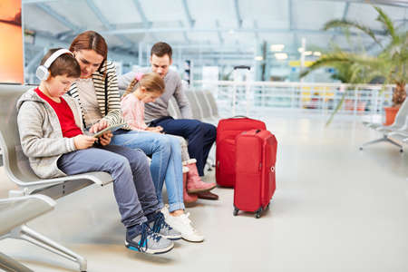 Family with children in airport terminal must wait for connecting flight in the rest area 免版税图像