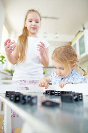 Two children build a stretch of dominoes on a table