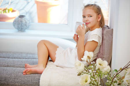 Child relaxing with a cup of tea at home 免版税图像