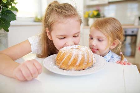 Two children taste a fresh cupcake in the kitchen 免版税图像