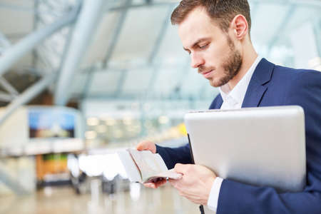 Young manager on business trip looks into his appointment book in airport terminal Foto de archivo