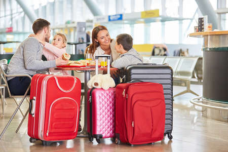 Family with children strengthens on the way to vacation in the airport restaurant
