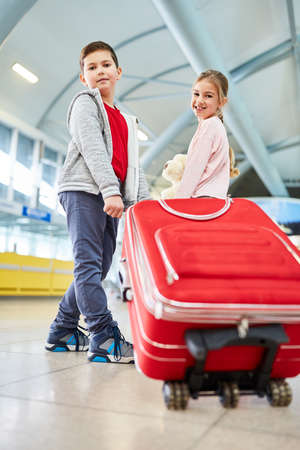 Siblings Children carrying a trolley on the way in the airport terminal or train station