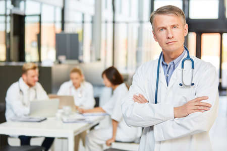 Man as chief physician with authority and self-confidence in front of his clinic doctors team 免版税图像