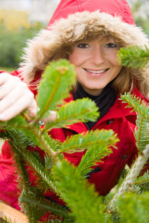 Blonde woman in winter clothes looks through the branches of a fir tree