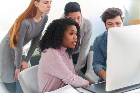 Multicultural web designer team and graphic designer on computer in office 免版税图像