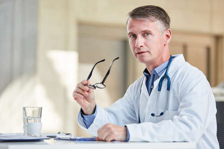 Man as chief physician or specialist with competence and experience in the hospital in the office