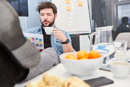 Business man takes a coffee break in the office with snacks and drinks on the table