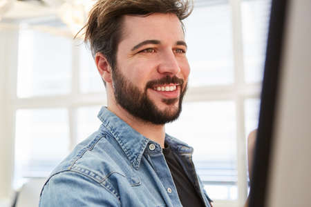 Smiling young business man as a successful start-up founder in the office