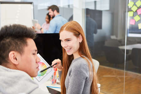 Young woman as a graphic designer in color design with a colleague in the design agency