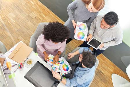 Graphic designer team in internet agency discusses color design of a website 免版税图像