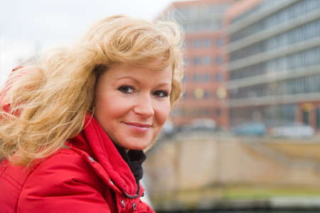 Portrait of a blonde woman on a bridge railing 免版税图像