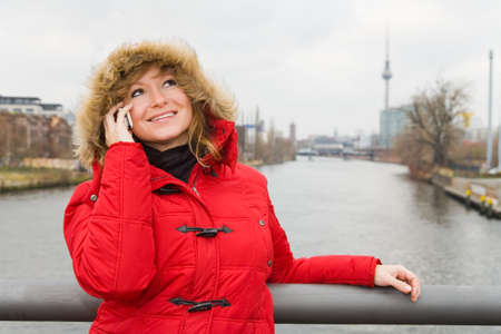 Blonde woman talking on the phone on a bridge over the Spree in Berlin, Germany