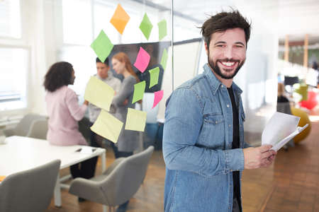 Happy start-up with papers in the office of his internet agency