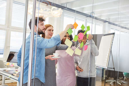 Students or young start-up team in the brainstorming workshop with notes on a glass wall