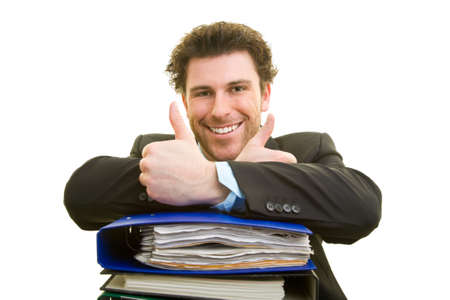 Young man in suit with a pile of files shows with both thumbs up