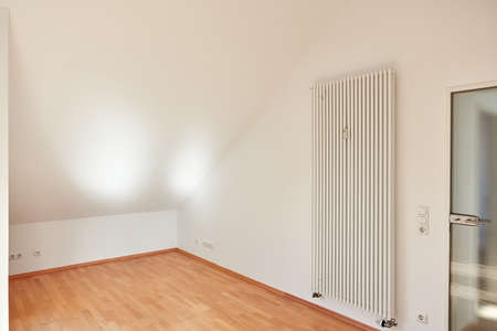 Empty bright room with sloping ceiling in attic apartment with radiator