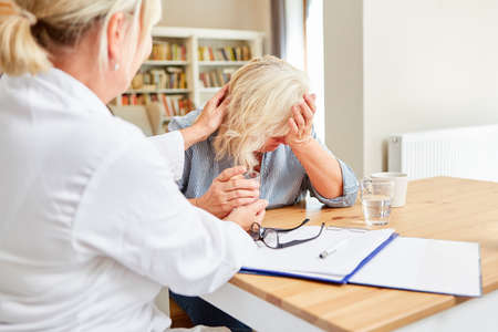 Crying senior patient is comforted by female doctor or nursing wife