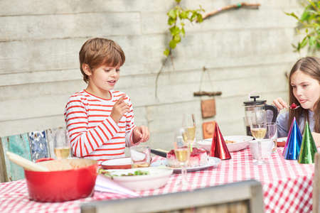 Two kids together at the table having food on a summer party in the garden