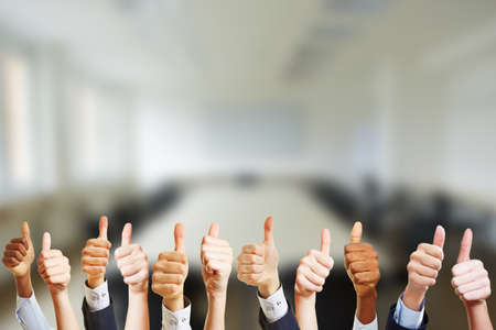 Business people hold thumbs up at work